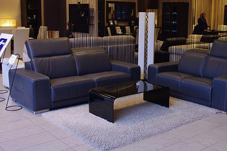 Domino - nowoczesny komplet wypoczynkowy, sofa czarna skórzana w aranżacji wnętrza salonu, do kompletu czarna ława szklana i szary włochaty dywan