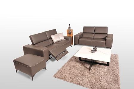 Aranżacja salonu z dwiema sofami skórzanymi w kolorze brązowym, komplet dopełnia elegancka pufa skórzana