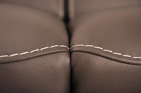 Ozdobne szycie brązowej skóry grubą nicią w kolorze białym