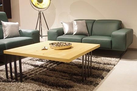 Ława na metalowej czarnej konstrukcji z dębowym blatem z litego drewna, w tle nowoczesna zielona sofa skórzana z grubymi bokami i pochylanymi zagłówkami