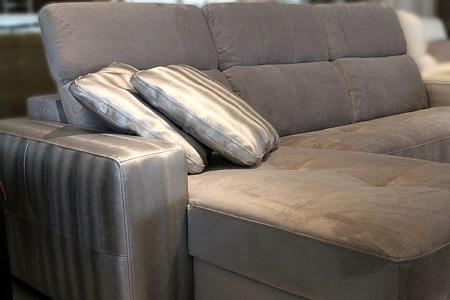 Drift - białe złote poduszki leżące na sofie tapicerowanej tkaniną w kolorze białego złota