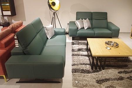 Aranżacja wnętrza nowoczesnego salonu - wygodne kanapy skórzane, zielone skóra butelkowa zieleń, białe poduszki, szary dywan włochacz, ława metalowa z blatem z litego drewna dębowego