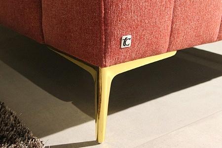 Złota nóżka w nowoczesnej sofie tapicerowanej tkaniną w kolorze czerwonym