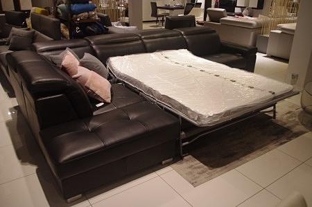 Czarny narożnik skórzany ze spaniem codziennym, system rozkładania spania typu Sedaflex, elegancki wypoczynek skórzany z pikowanymi siedziskami i regulowanymi zagłówkami