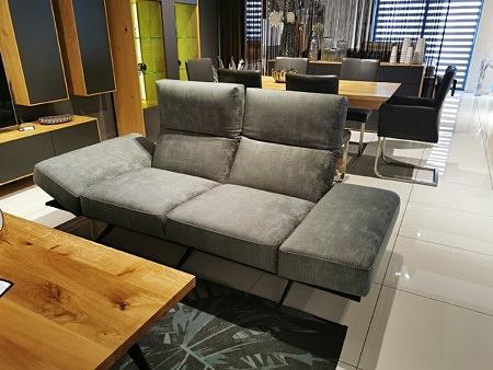 Szara sofa z regulowanymi bokami na metalowych nogach